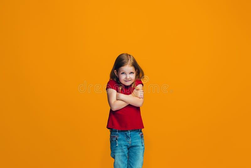 Härlig tonårig flicka som ser förvånad och förbryllad isolerat på apelsinen royaltyfri foto