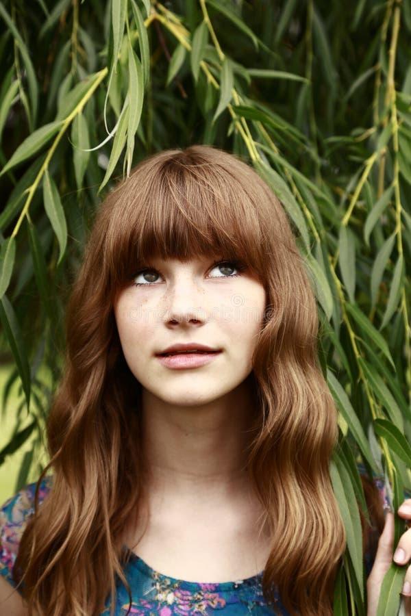 Härlig tonårig flicka som ser upp arkivfoto