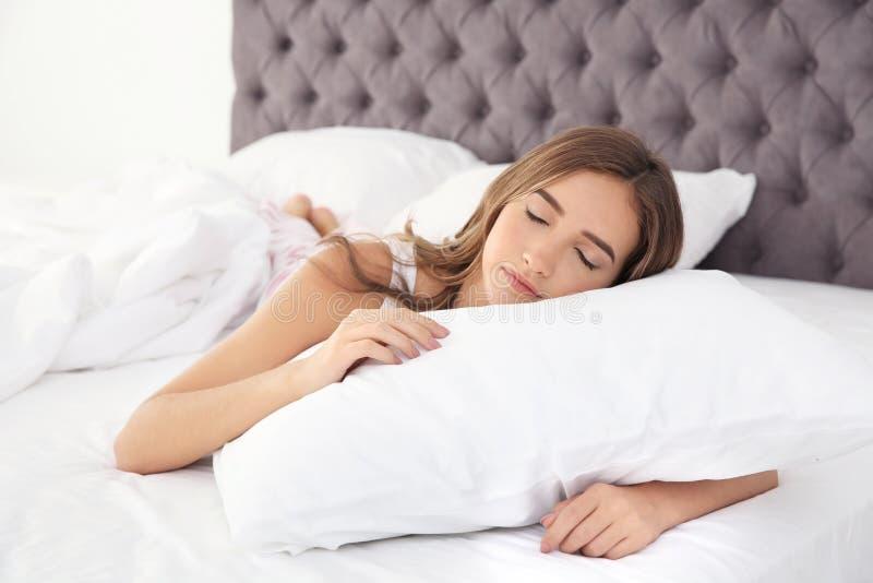 Härlig tonårig flicka som sover med den bekväma kudden i säng royaltyfri foto