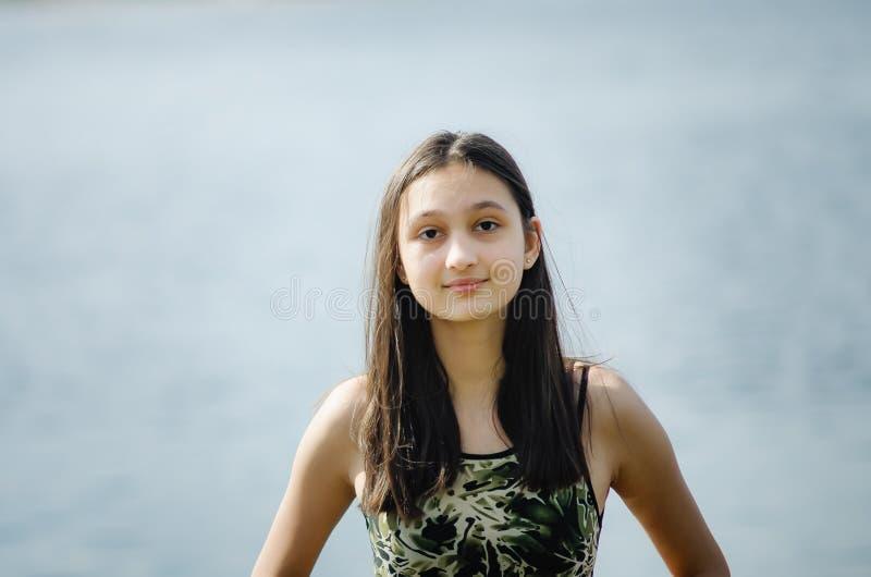 Härlig tonårig flickabrunett med långt hår på bakgrund för blå himmel royaltyfria foton
