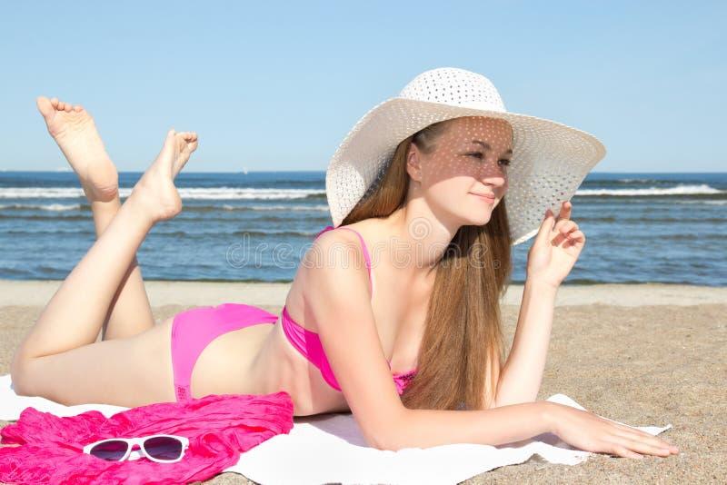 Härlig tonåring i rosa bikini och vithatten som ligger på beaen fotografering för bildbyråer
