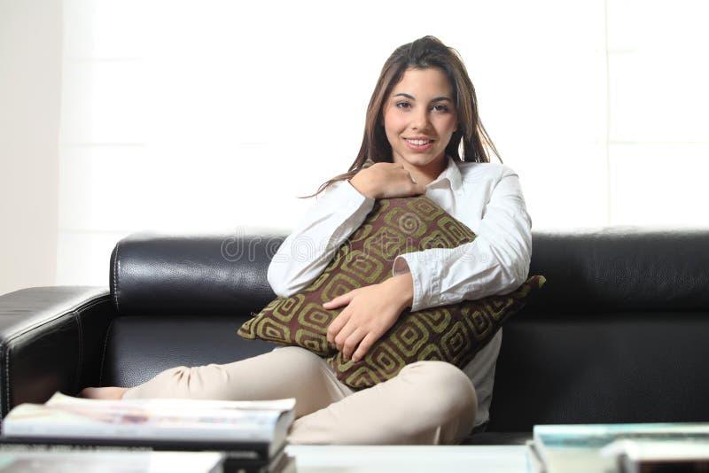 Härlig tonåring på en soffa hemma som omfamnar en dämpa royaltyfri fotografi