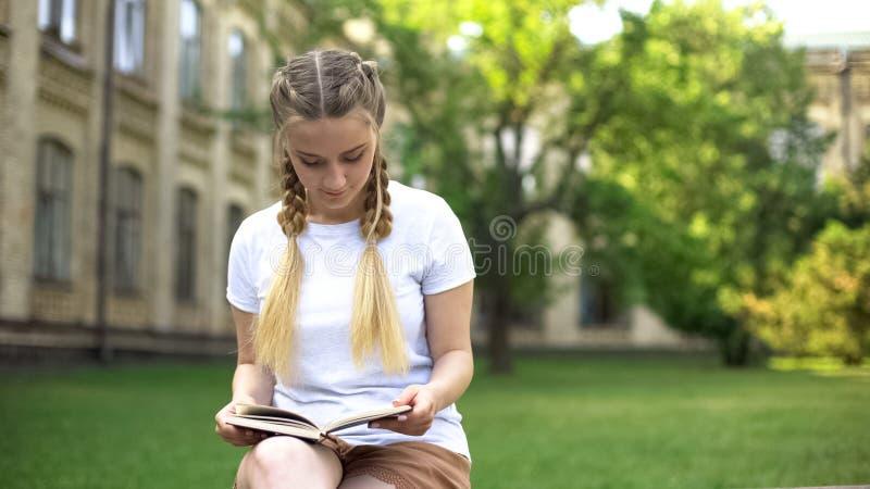 Härlig tonåringflickaläsebok på bänk i universitetsområdet som förbereder läxa arkivbild