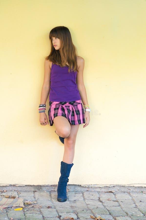 Härlig tonårs- flicka i kort kjol och kängor som står utomhus- arkivbild