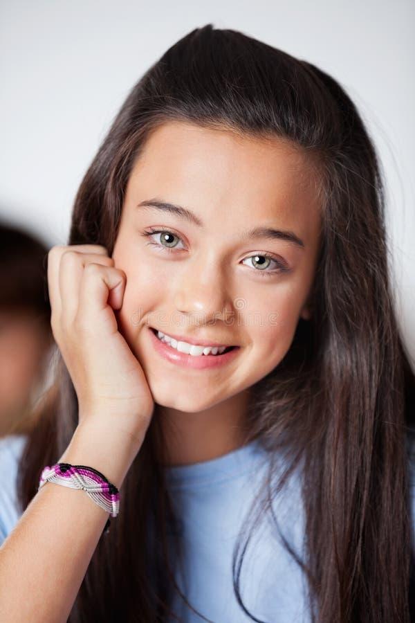 Härlig tonårs- skolflicka, i att le klassrumet royaltyfri bild