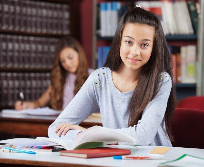 Härlig tonårs- skolflicka med böcker som in sitter arkivfoton