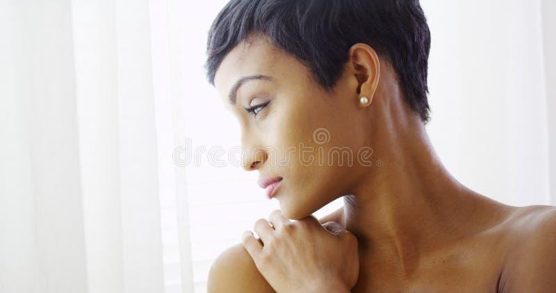 Härlig topless svart kvinna som kramar sig och ut ser fönstret arkivbilder