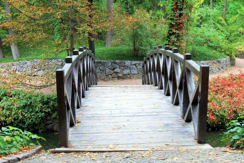 Härlig träbro över en liten flod i hösten Sofia Park royaltyfri foto