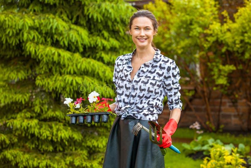 Härlig trädgårdsmästare med blommor och hjälpmedel royaltyfria foton