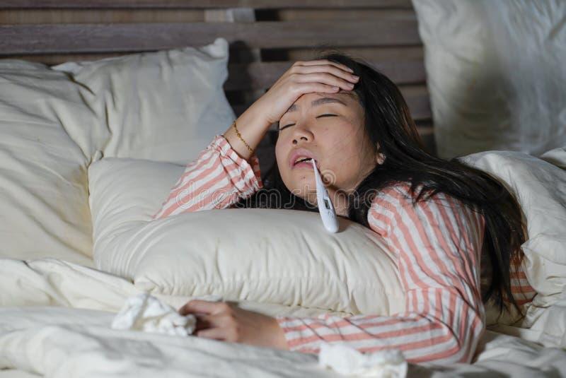 Härlig trött och dåligt asiatisk kinesisk kvinna som ligger på hemmastadd febriga sjuk lida kall influensa för säng och huvudvärk royaltyfria foton