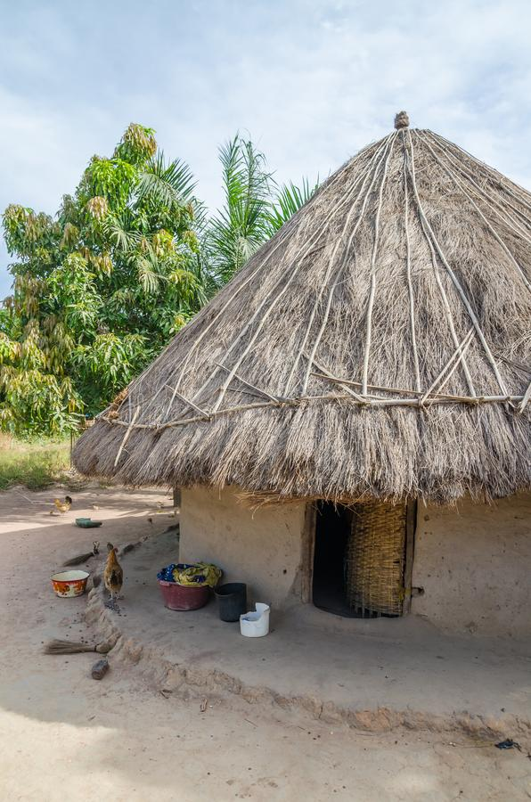 Härlig traditionell halmtäckt rund gyttja och lera förlägga i barack i lantlig by av Guinea Bissau, Västafrika royaltyfri bild