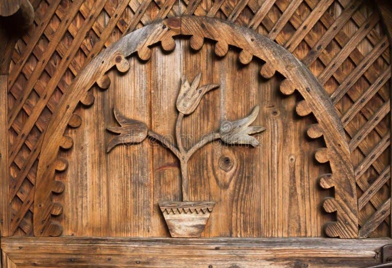 Härlig traditionell prydnad i form av tulpan från en hand - gjord dörr från ingången i ett rumänskt hushåll royaltyfria foton