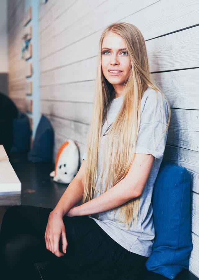 Härlig trendig blond flicka med långt hårsammanträde på en tabell i ett trendigt kafé för hipster som ut ser fönstret royaltyfri bild