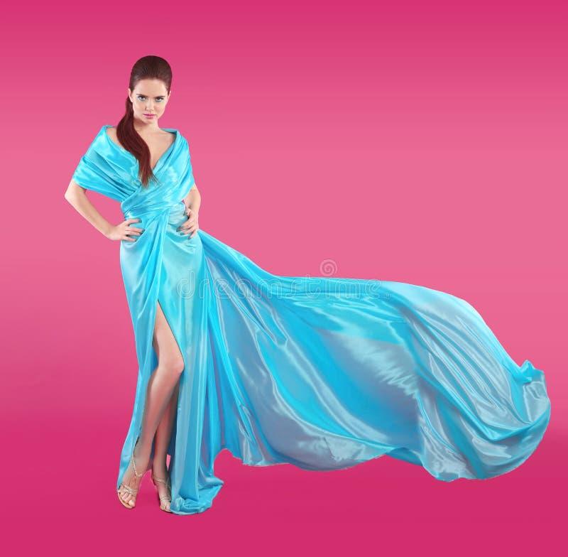 Härlig trendig flicka, i att blåsa blåttklänningen Kvinna i Flyin royaltyfria foton
