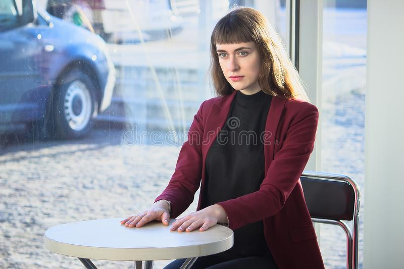 Härlig trendig flicka på en tabell i ett kafé arkivbild