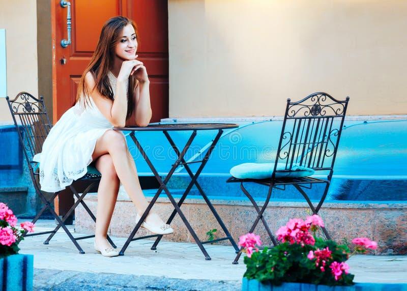 Härlig trendig flicka på en tabell i ett kafé Restaurang i gatan royaltyfri foto
