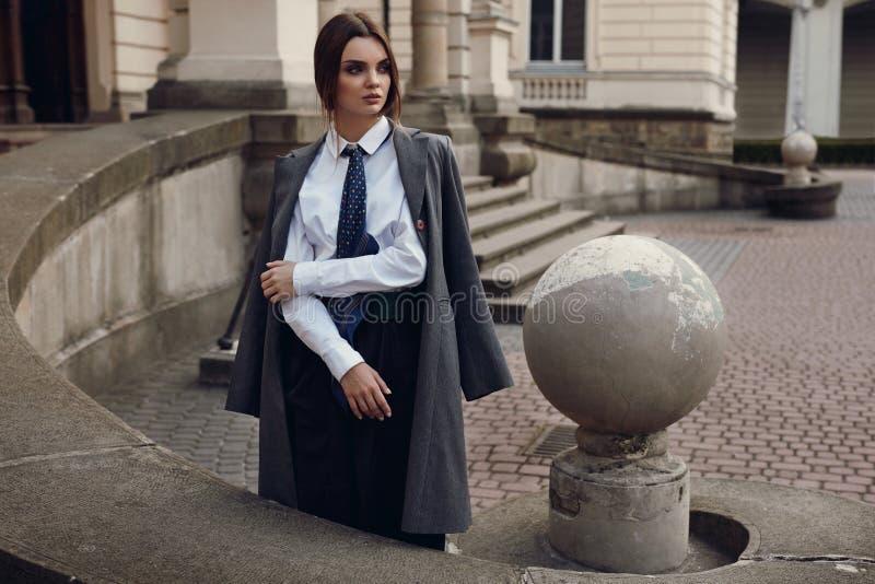 Härlig trendig kvinna i modekläder som poserar i gata royaltyfri fotografi