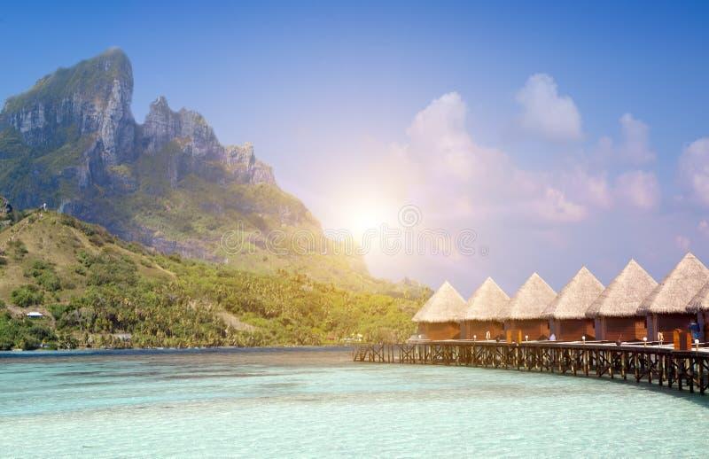 Härlig tropisk Maldiverna ö, vattenvillor, bungalow på havet och berget på en bakgrund fotografering för bildbyråer