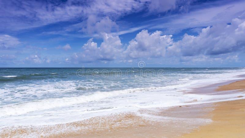 Härlig tropisk sandig strand med bakgrund för blått hav och för blå himmel och våg som kraschar på sandig kust royaltyfri bild