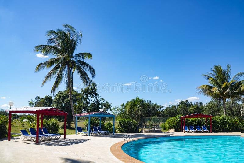 Härlig tropisk semesterort med simbassängen, sol-dagdrivare och palmträd under en varm solig dag, semestrar i Kuba royaltyfri bild