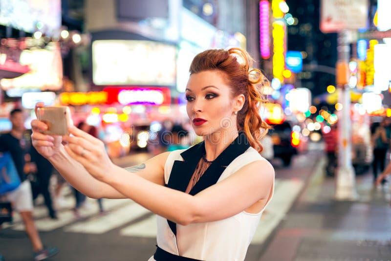 Härlig turist- kvinnamodeblogger som tar fotoselfie på nattetidfyrkant i New York City fotografering för bildbyråer