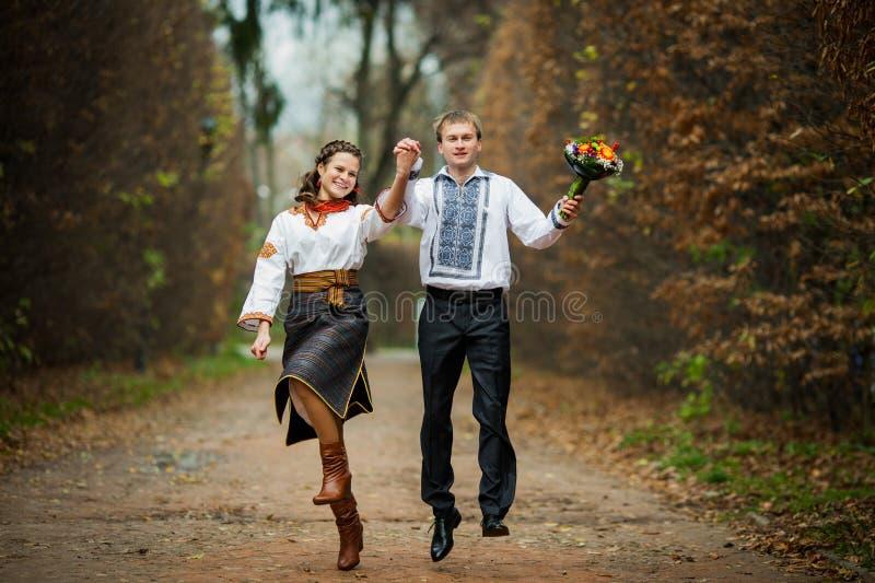 Härlig ukrainsk brud- och brudgumbanhoppning i infödd broderi royaltyfri foto