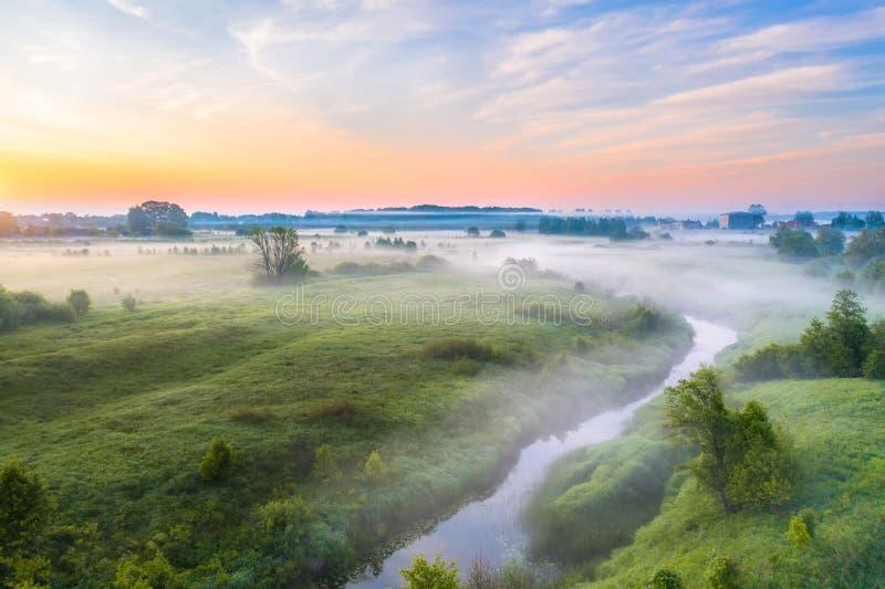 Härlig underjordisk dimma över en liten flod bland gräs- ängar i landsbygder, tidigt på morgonen på gryning royaltyfri bild