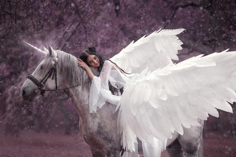 Härlig ung älva som går med en enhörning Hon bär ett oerhört ljus, den vita klänningen Konsthotography royaltyfria foton