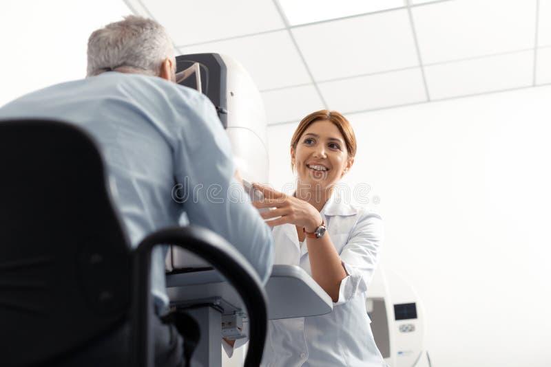 Härlig ung ögondoktor som ler, medan undersöka den pensionerade mannen arkivfoton