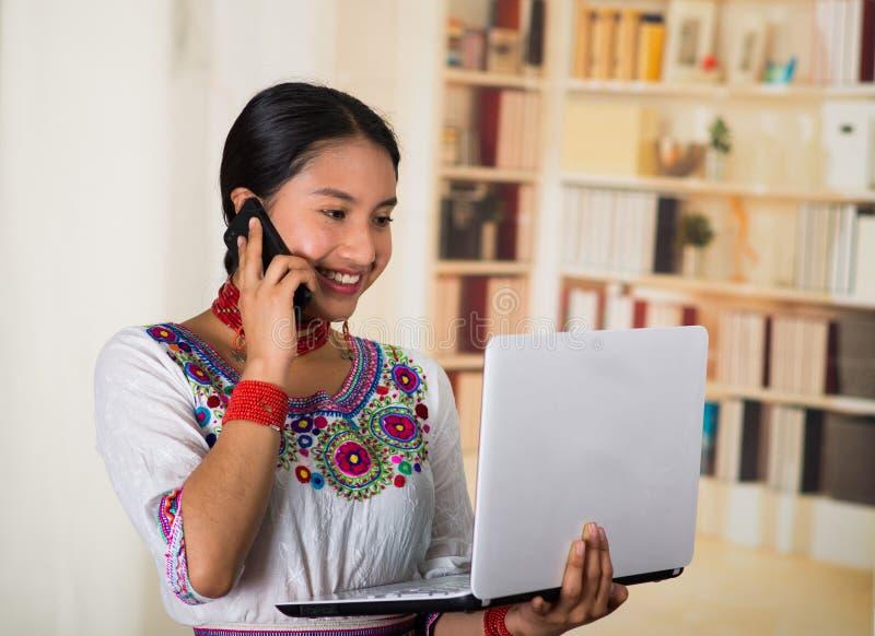 Härlig ung advokat som bär den traditionella andean blusen och den röda halsbandet, hållande bärbar dator som talar på att le för arkivbilder