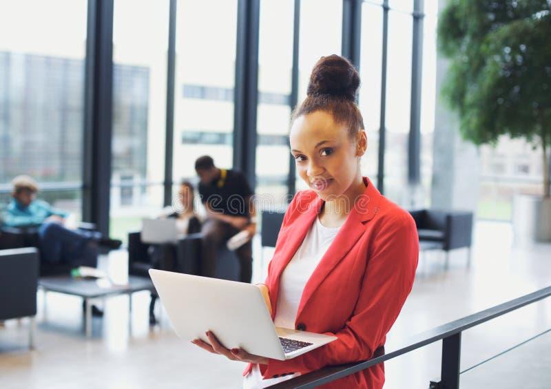 Härlig ung affärskvinna med bärbara datorn i modernt kontor royaltyfri fotografi
