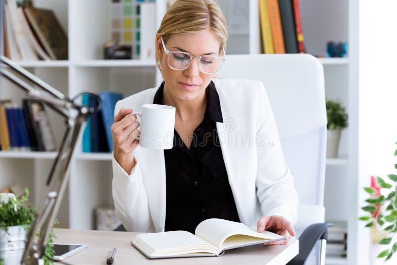 Härlig ung affärskvinna som dricker kaffe, medan granska hennes dagbok i kontoret arkivbilder