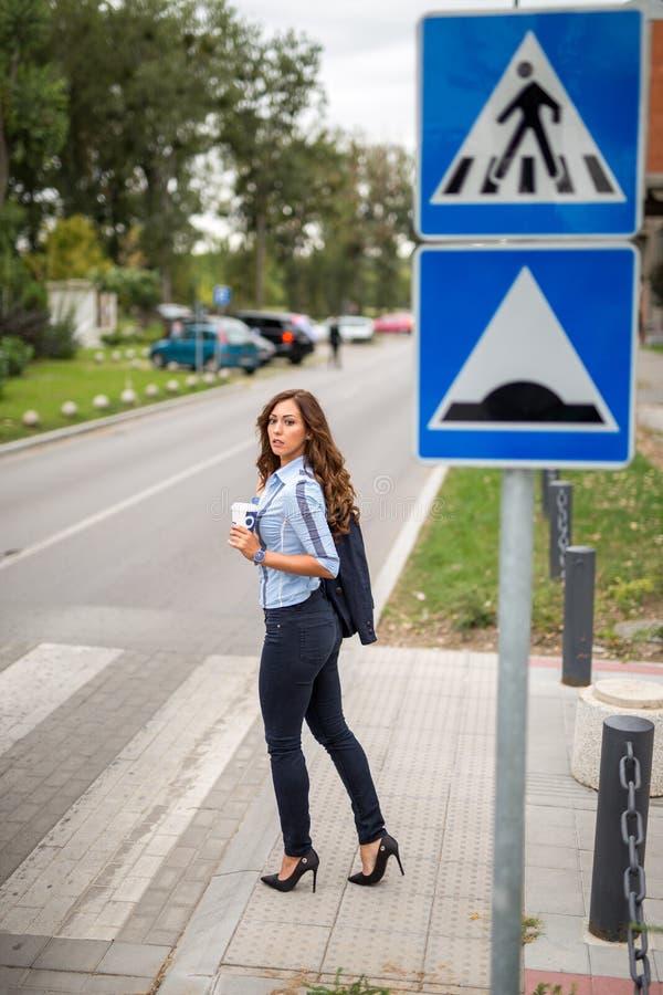 Härlig ung affärskvinna som korsar en gata på en gångare royaltyfria foton