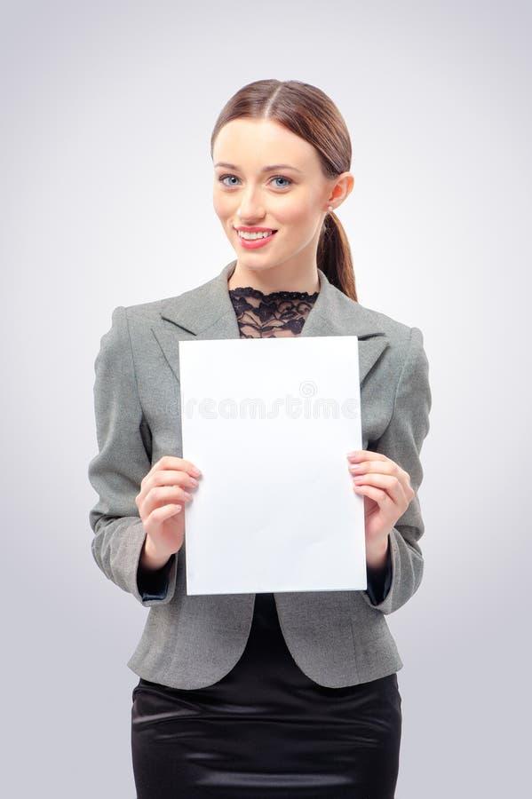 Härlig ung affärskvinna som rymmer det tomma kortet royaltyfria bilder