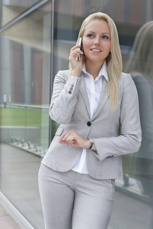 Härlig ung affärskvinna som samtalar på mobiltelefonen, medan luta på glasväggen royaltyfria bilder