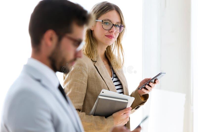 Härlig ung affärskvinna som ser kameran och använder mobiltelefonen bredvid hennes partner i ett hall av dem företag arkivbilder