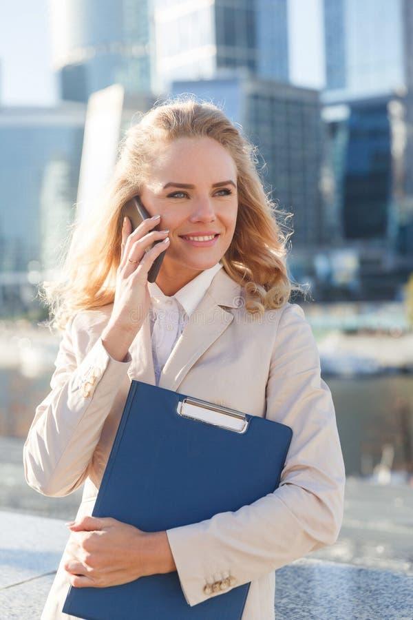 Härlig ung affärskvinna som talar på smartphonen och lyckligt le arkivfoton