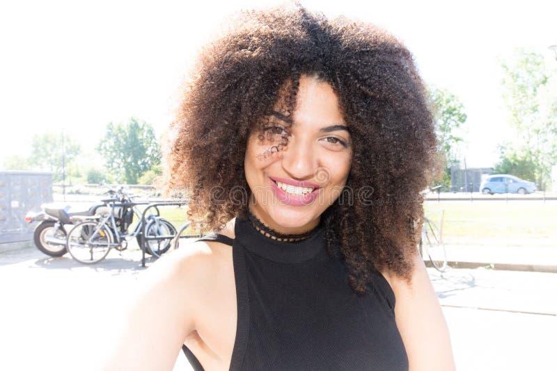 Härlig ung afrikansk amerikankvinna som ler i gatastad arkivbilder