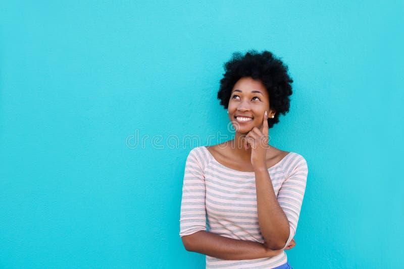 Härlig ung afrikansk kvinna som ler och tänker royaltyfria foton
