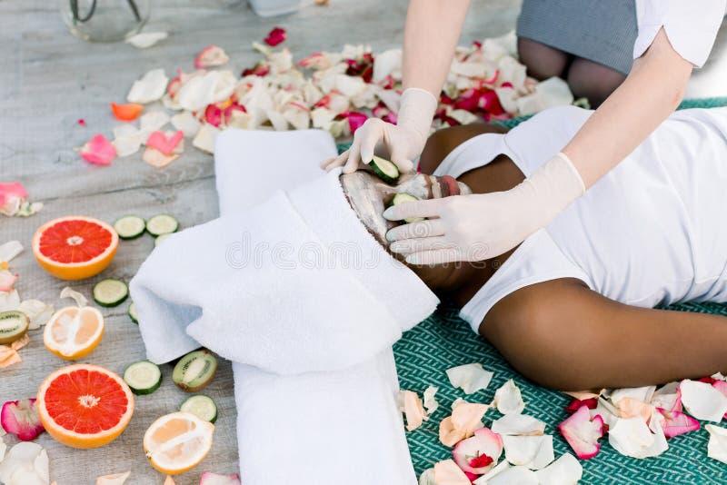 Härlig ung afrikansk kvinna som mottar den ansikts- maskeringen och gurkor på ögon i skönhetsalong, händer av cosmetologisten royaltyfria bilder