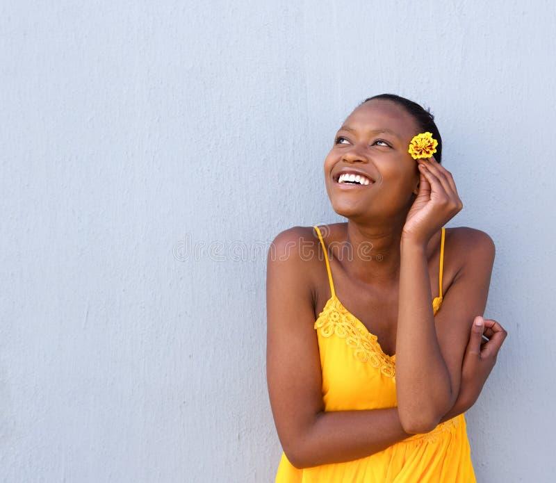 Härlig ung afrikansk kvinna som rymmer en blomma arkivbild
