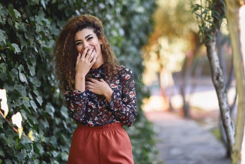 Härlig ung arabisk kvinna som skrattar i stads- bakgrund arkivfoton