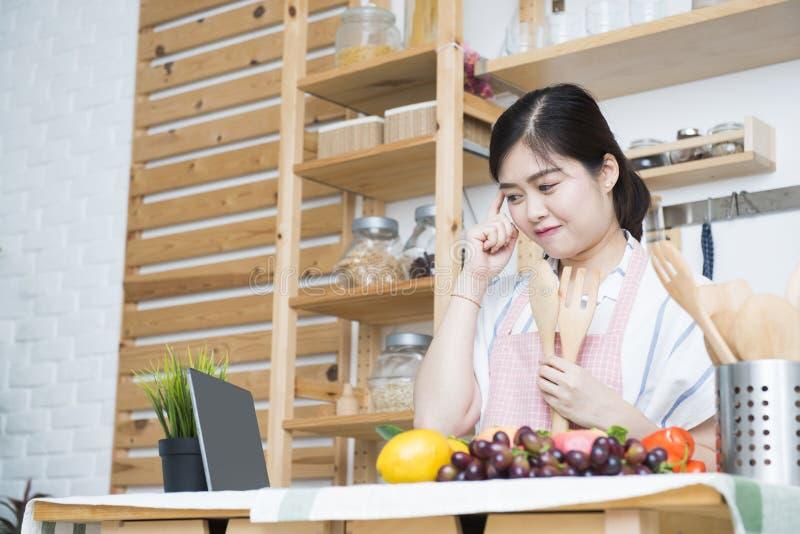 Härlig ung asiatisk dator för kvinnabruksminnestavla som ska lagas mat i kök, en fingerpunkt på pannan med tänkande position arkivbild