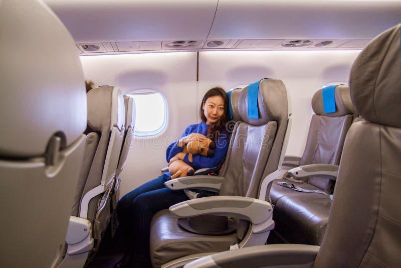 Härlig ung asiatisk flicka som bekvämt sitter på platsen och ser smartphonen i kabinen och le royaltyfri bild