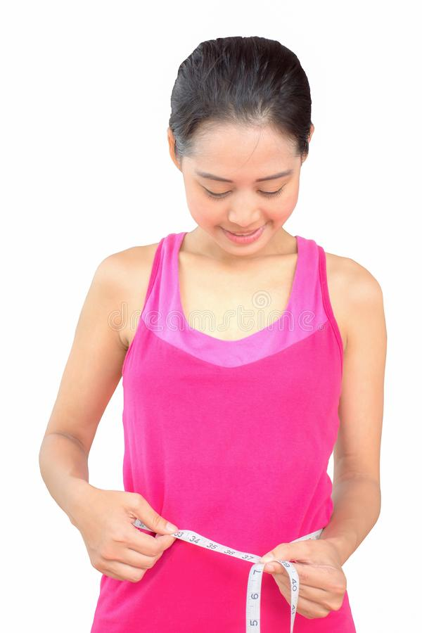 Härlig ung asiatisk flicka som mäter hennes midja med måttbandet royaltyfria foton