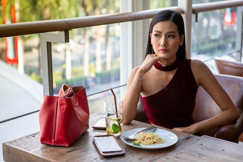 Härlig ung asiatisk kvinna i den röda klänningen som sitter i restaurangen som ut ser fönstret elegant dam som sitter på att tänk fotografering för bildbyråer