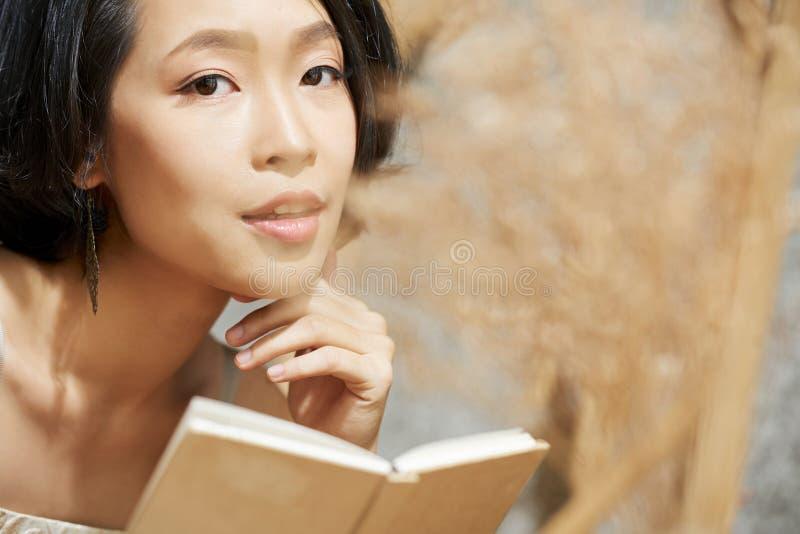 Härlig ung asiatisk kvinna med den lilla boken royaltyfria bilder