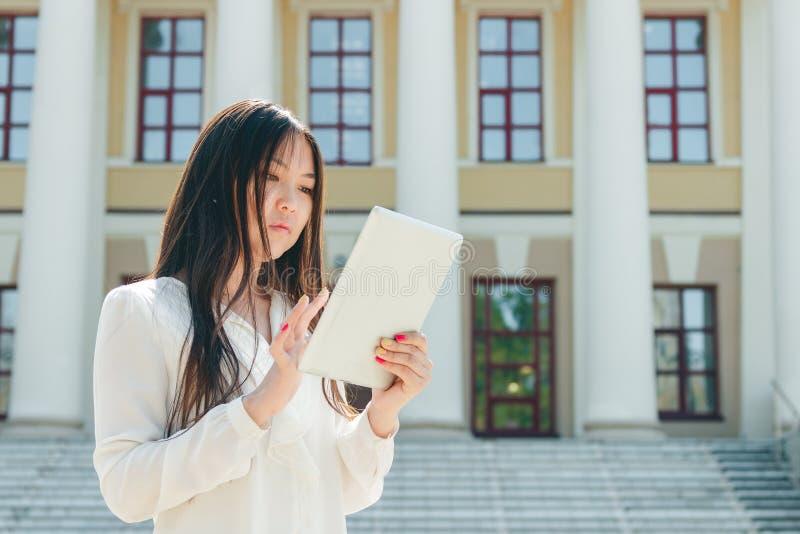 Härlig ung asiatisk kvinna som använder minnestavladatoren royaltyfria foton