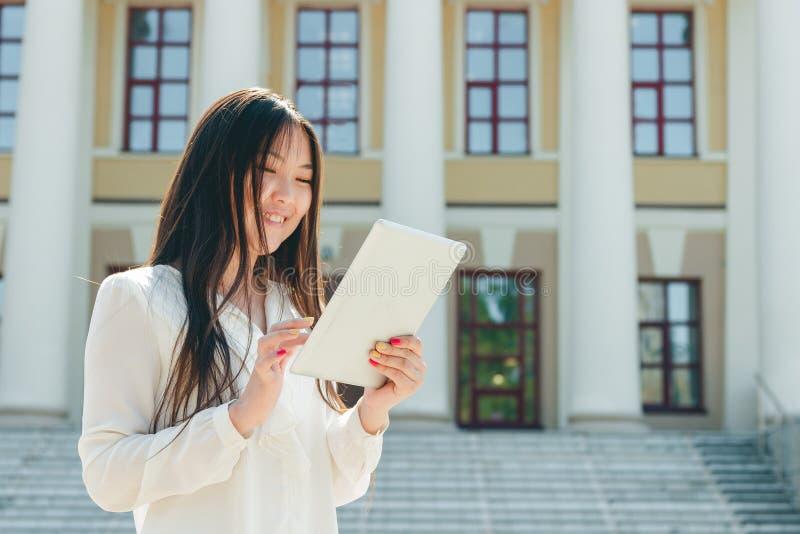 Härlig ung asiatisk kvinna som använder minnestavladatoren fotografering för bildbyråer