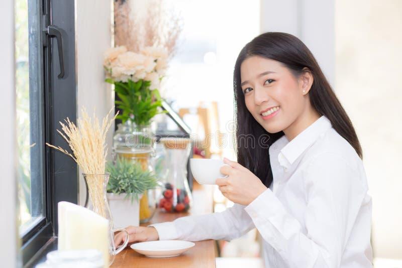 Härlig ung asiatisk kvinna som dricker kaffe och leende i morgonen på kafét, flickasammanträde i coffee shop royaltyfria foton